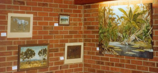 Four paintings from the exhibition. The right hand one is of a tropical pool.