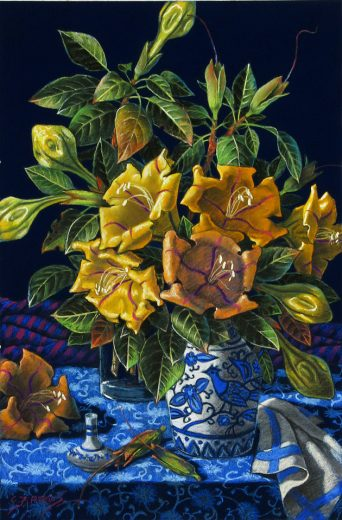 Yellow flowers, leaves and buds are in a blue pottery jug.